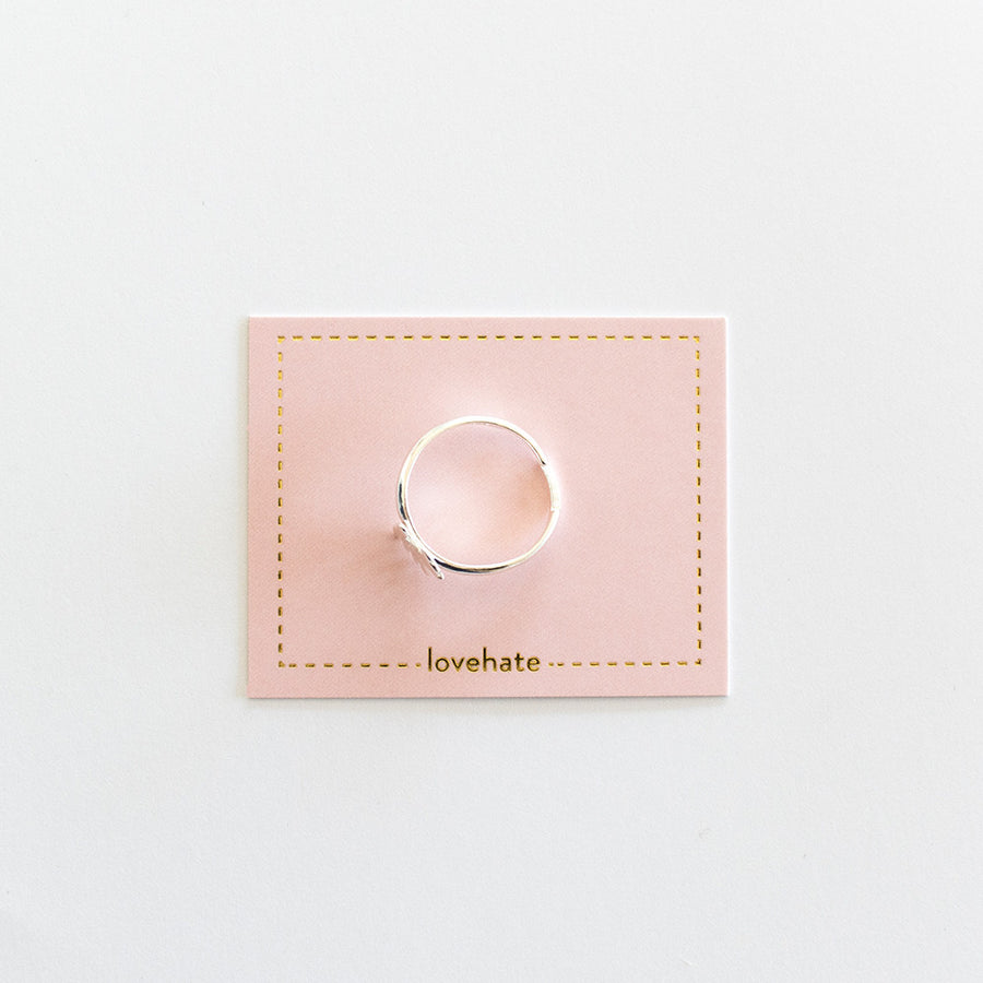 A sterling silver childrens adjustable sized ring on a pink card with gold trim, all on a grey background