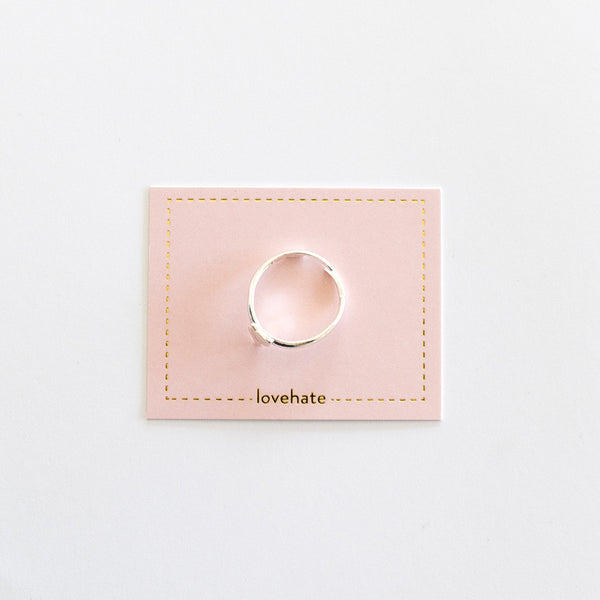 A childrens adjustable size sterling silver ring with a small fox on a pink card with gold trim, against a grey background