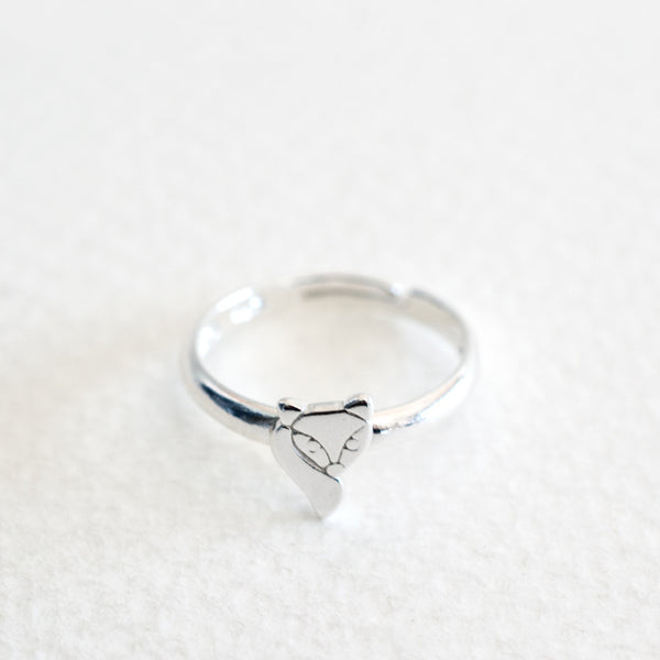 A childrens adjustable size sterling silver ring with a small fox, against a grey background