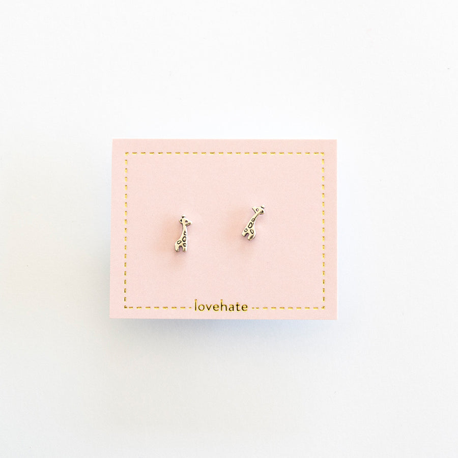 A pair of sterling silver stud earrings in a giraffe shape on a pink card