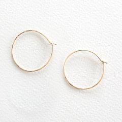 A pair of lightly hammered gold hoop earrings on a grey background