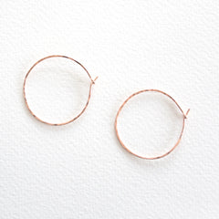 A pai of lightly hammered rose gold hoop earrings with simple clasp on grey background
