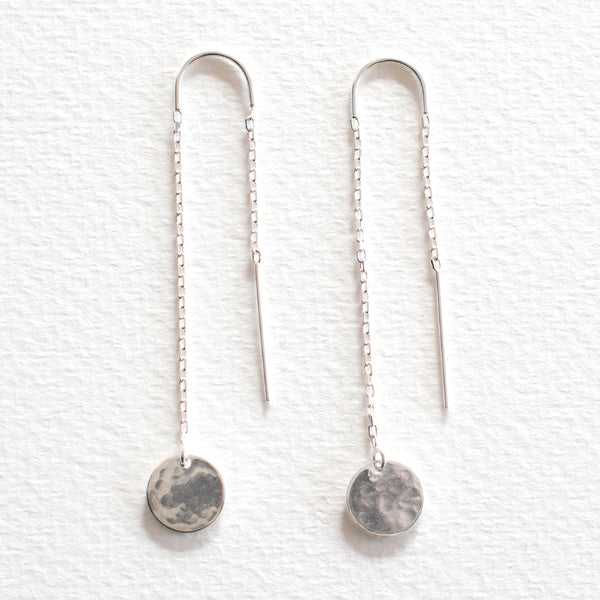 A pair of 925 Sterling Silver Thread Earrings with small, circular, hammered discs, on a grey background