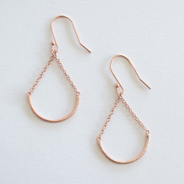 A pair of Rose Gold Plated 925 Sterling Silver Drop Earrings with U shaped hand twisted wire on delicate chain, on a grey background.