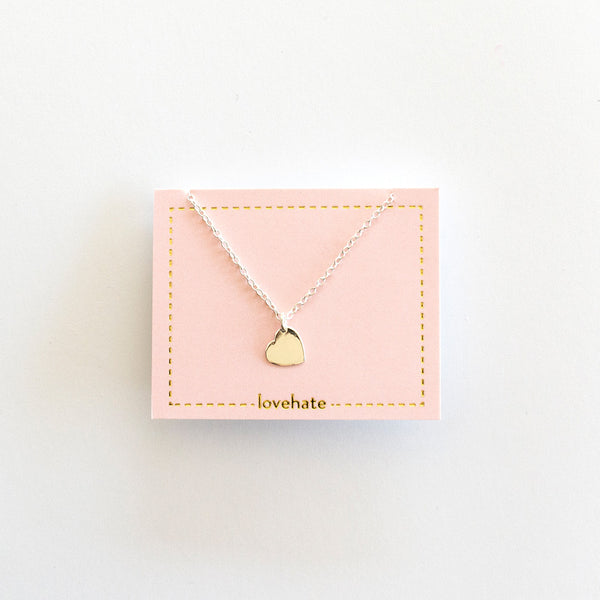 A sterling silver necklace with a small heart pendant on a pink card