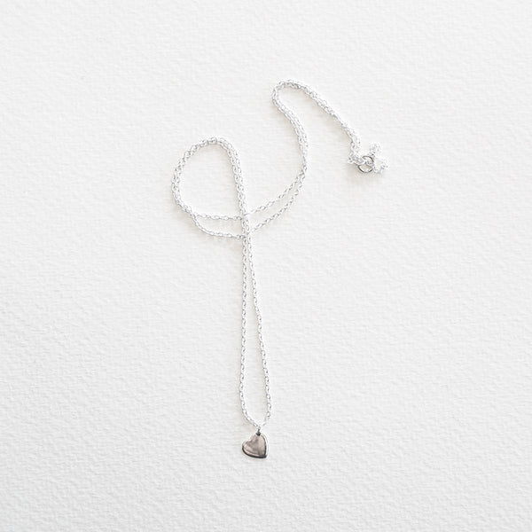A fine chain with a small heart pendant in sterling silver, on a grey background