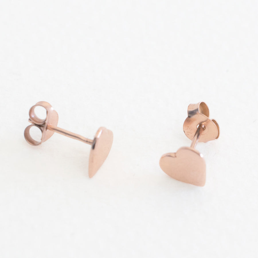 A pair of rose gold plated sterlings silver heart shaped stud earrings on a grey background