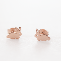 A pair of rose gold plated 925 sterling silver bunny rabbit stud earrings on a grey background