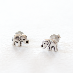 A pair of sterling silver elephant shaped stud earrings sit on a grey background