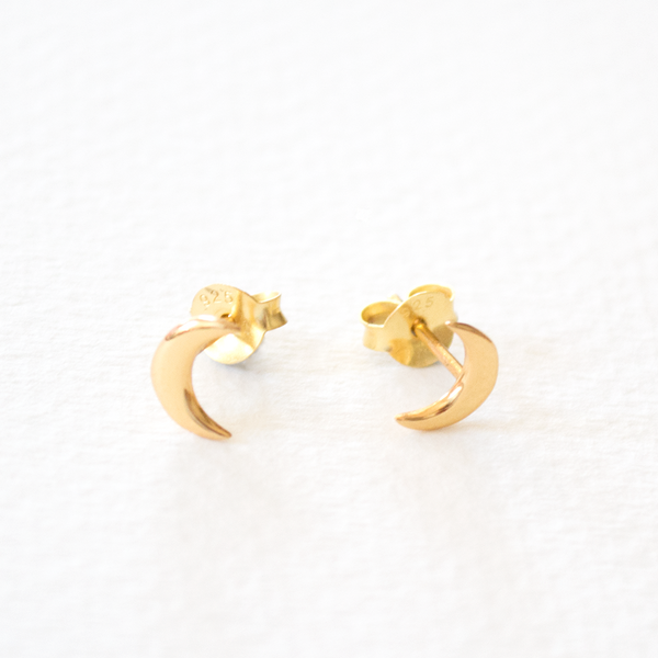 A pair of gold plated sterling silver moon shaped stud earrings on a grey background