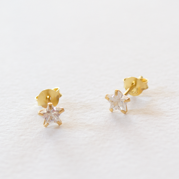 A pair of star shaped sparkly cubic zirconia stud earrings with 18ct gold plated sterling silver setting on a grey background