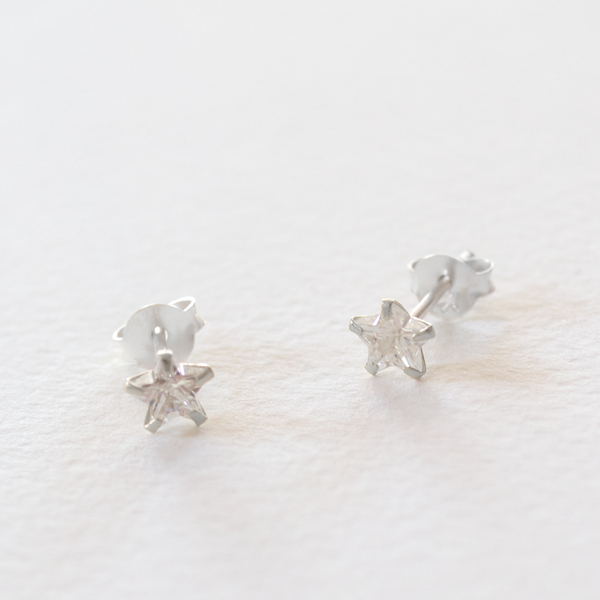 A pair of sparkly star shaped cubic zirconia stud earrings with sterling silver setting on a grey background