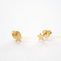 A pair of small gold star shaped stud earrings on a grey background
