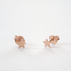 A pair of rose gold star shaped stud earrings on a grey background