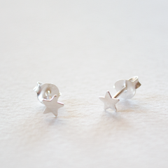 A pair of sterling silver star shaped stud earrings on a grey background