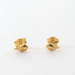 A pair of gold whale shaped stud earrings on a grey background