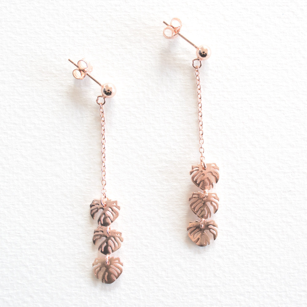 5c3824ebf A pair of rose gold drop earrings with monstera leaves ...