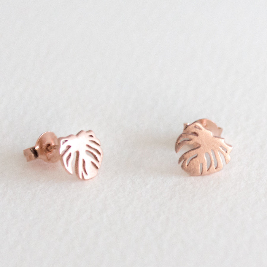 A pair of rose gold monstera leaf stud earrings on a grey background