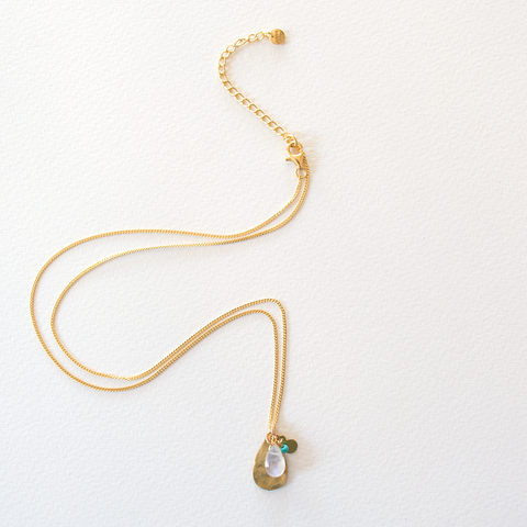 A hammered brass and rainbow moonstone tear drop necklace on a gold plated sterling silver chain