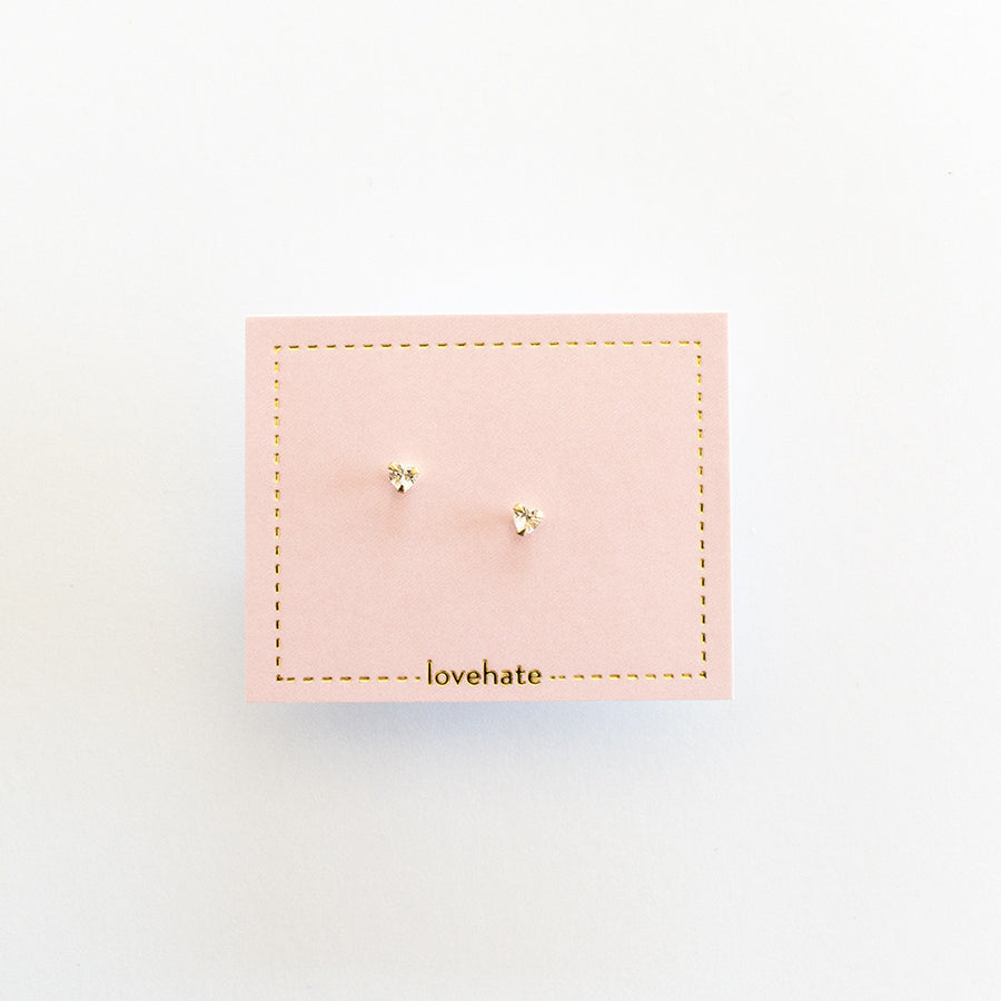 A pair of gold heart shaped crystal earrings on a pink card