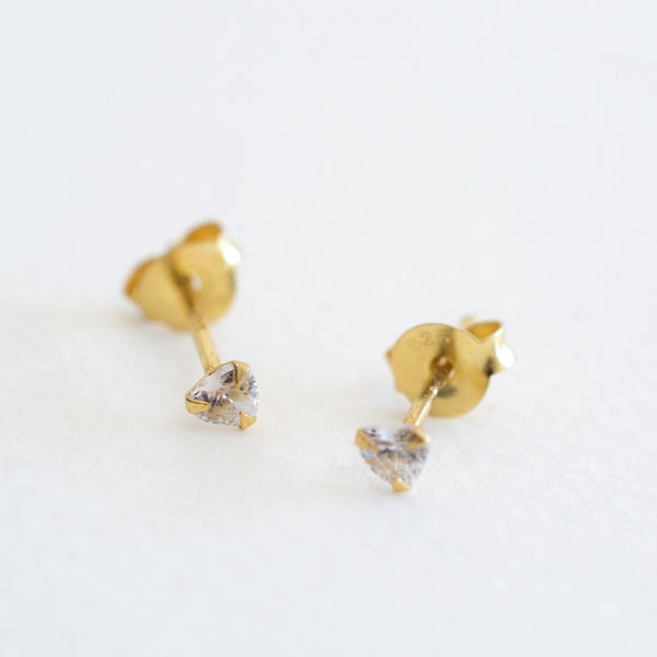 A pair of heart shaped crystal studs made from cubic zirconia and gold plated sterling silver on a grey background