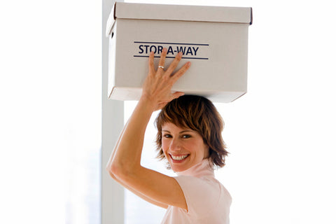 photo of smiling woman carrying box