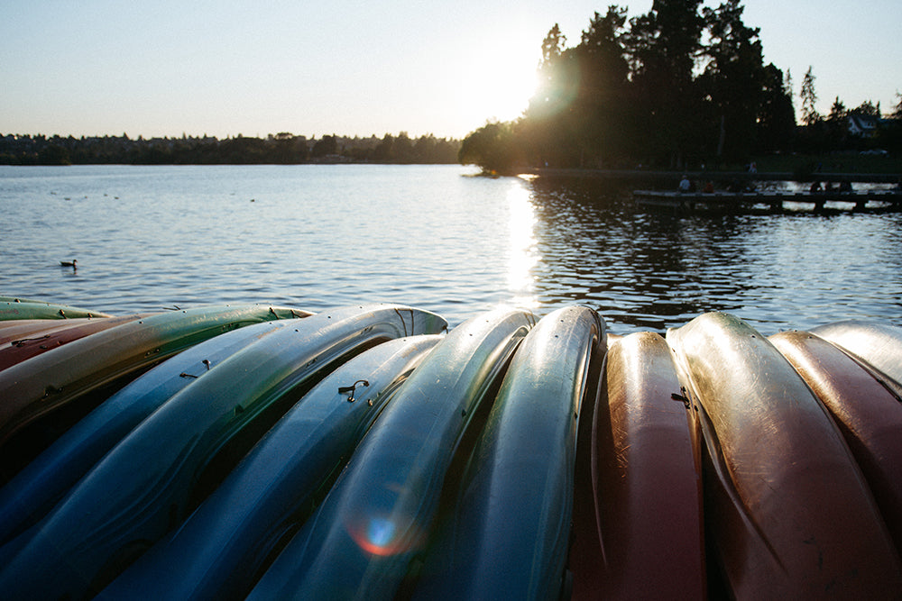 Canoes stacked by a lake.
