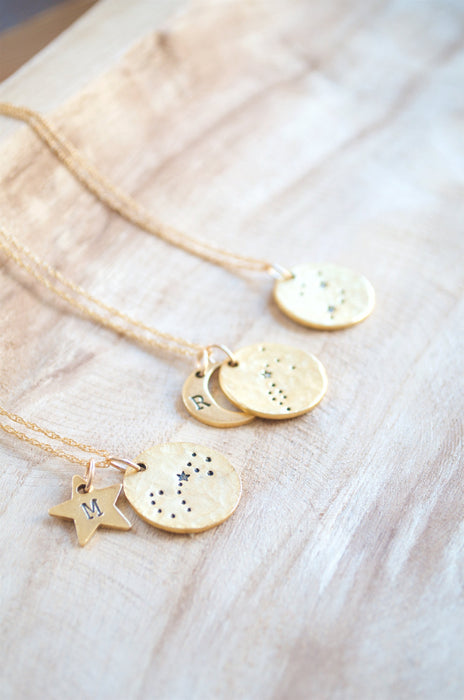 Three zodiac constellation necklaces on wooden plate.