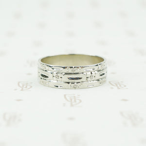 wide white gold band with forget me nots