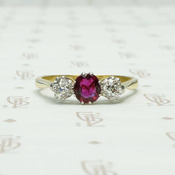 old mine cut diamonds sit to either side of a rich red oval ruby the 3 stone setting is platinum on 18k yellow gold