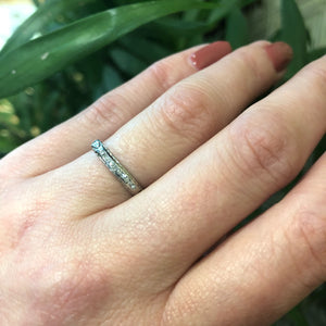 channel set diamond white gold band with arrow design on hand