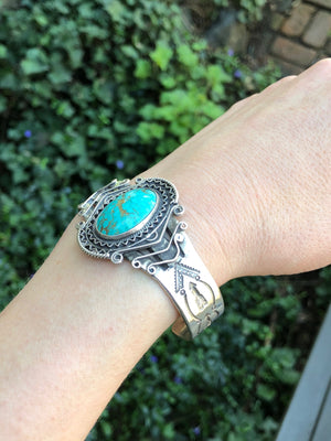 american silver cuff with arrow pattern and big turquoise on wrist