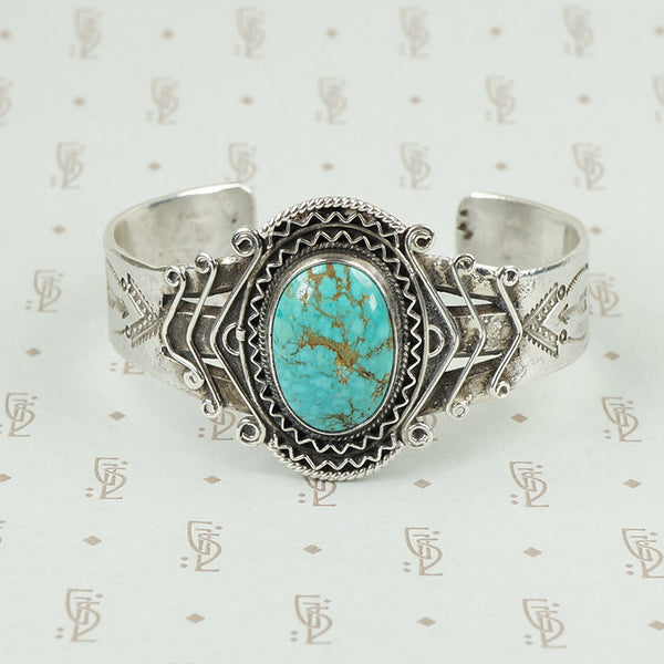 american silver cuff with arrow pattern and big turquoise