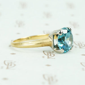 Natural blue zircon solitaire in palladium and 14k yellow gold side view