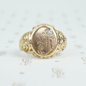 Gold signet ring with engraved j topped with a mine cut diamond
