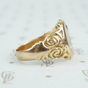 Gold signet ring with engraved j topped with a mine cut diamond side detail of scrolls