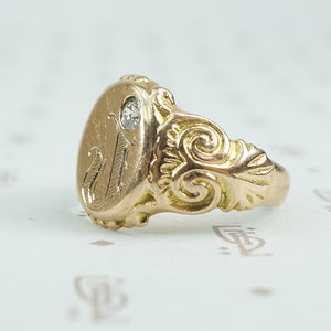 Gold signet ring with engraved j topped with a mine cut diamond side view