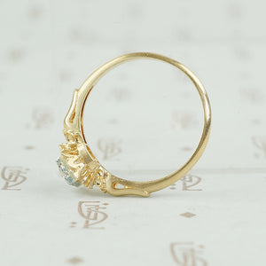 yellow gold flower holds white gold set diamond engagement ring