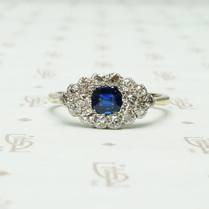 a cushion cut indigo blue natural sapphire is set east west amid a group of diamonds in an eye shaped platinum on 18k yellow gold ring