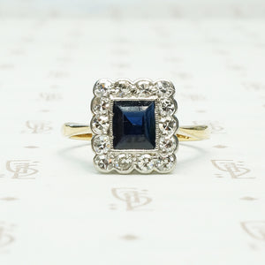 an emerald cut .60ct inky blue sapphire framed by diamonds in 18k yellow gold and platinum