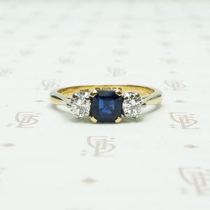 square sapphire set between 2 round white natural diamonds 18k yellow gold and platinum 3 stone ring