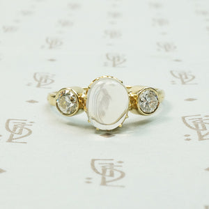 vintage moonstone in its original setting flanked by bezel set old diamonds in 14k recycled yellow gold ring