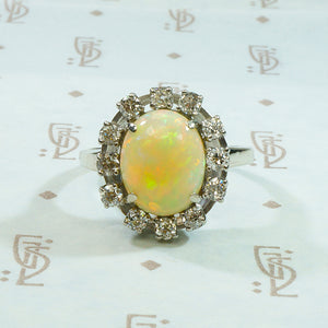 bright and firey oval opal surrounded by diamonds in 14k white gold ring