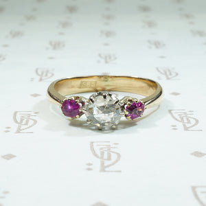 oval natural red rubies are set to either side of a round rose cut diamond in 14k gold