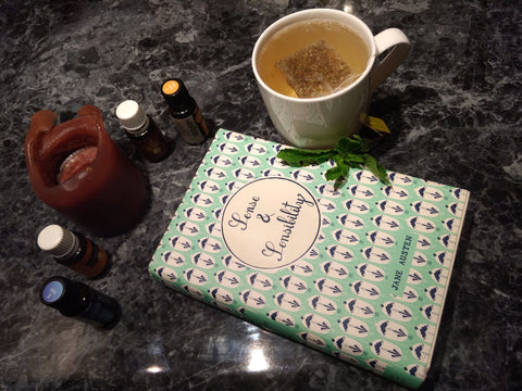 Note book with sense and sensibility written on it surrounded by a cup of tea and a candle