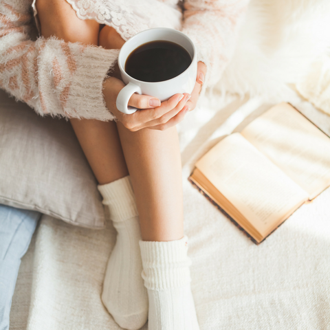 woman sitting with a cup of coffee and a book
