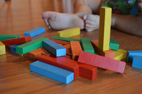 Differnt colored blocks with a child sitting behind them