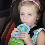 Young Girl sitting in a car seat eating from a reusable food pouch