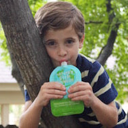 Young boy hanging from a tree eating a reusable food pouch