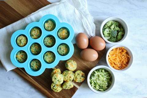 baby food freezer tray with fritters beside it and ramekins filled with cheese, broccoli, and eggs
